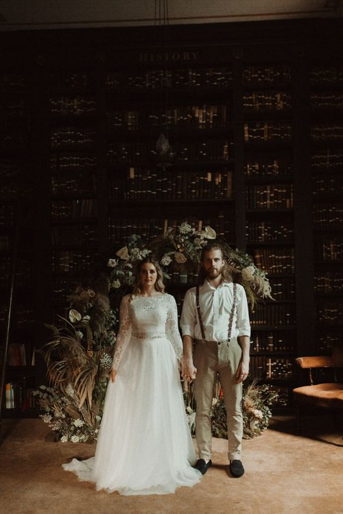 Bride in Separates and Groom in Chinos and Braces Standing in Front of a Dried Flower Moon Gate