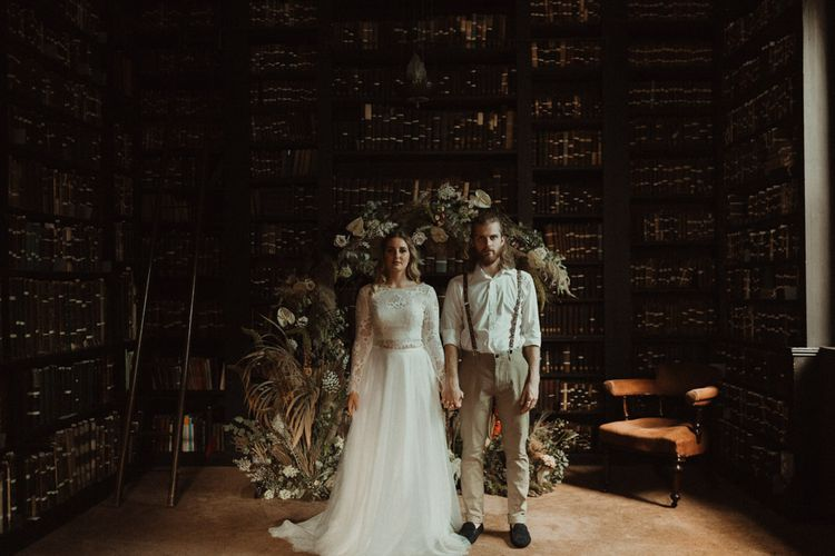 Bride in Separates and Groom in Chinos and Braces Standing in Front of a Dried Flower Moon Gate Holding Hands
