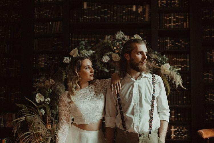 Bride in Separates and Groom in Chinos and Braces Standing in Front of a Dried Flower Moon Gate Embracing
