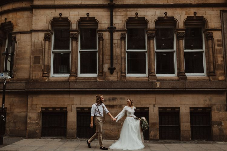 Bride in Separates and Groom in Chinos and Braces Holding Hands Walking Through Manchester Streets