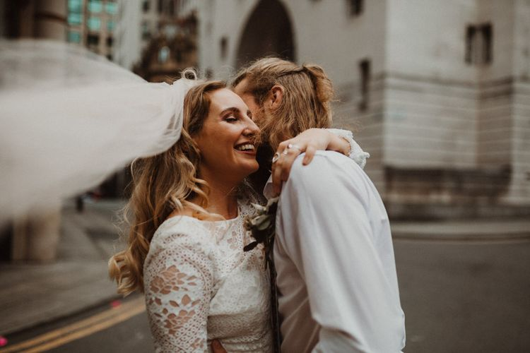Bride in Separates and Groom in Chinos and Braces Embracing in Manchester Streets