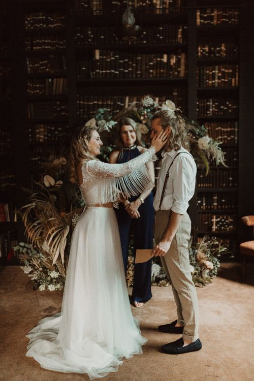 Elopement Wedding Ceremony with Bride in Fringe Sleeve Top Holding Her Grooms Face