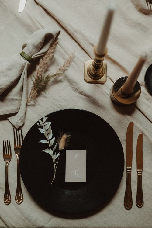 Contemporary Place Setting with Black Tableware and Gold Cutlery
