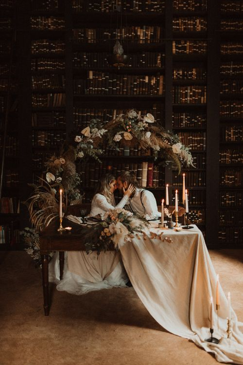 Boho Couple Sitting at Sweetheart Table Decorated with Linen Tablecloth and Taper Candles