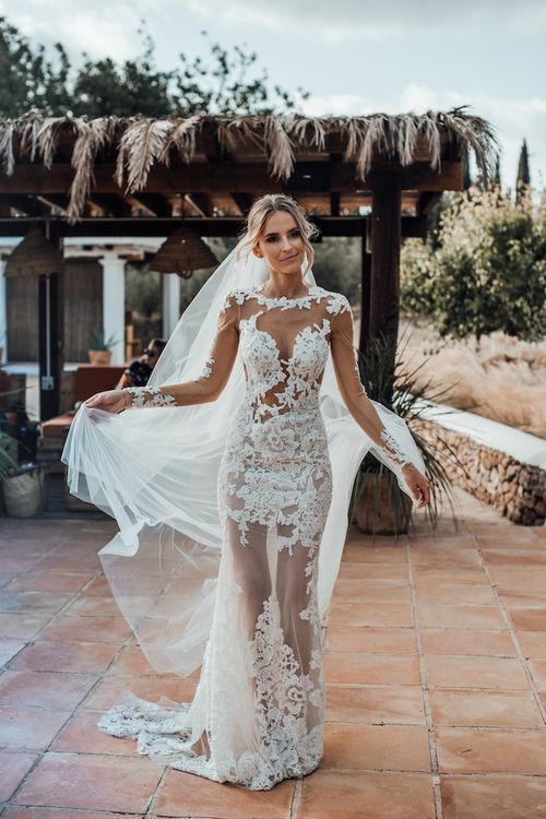 Stylish bride in sheer lace wedding dress with long sleeves