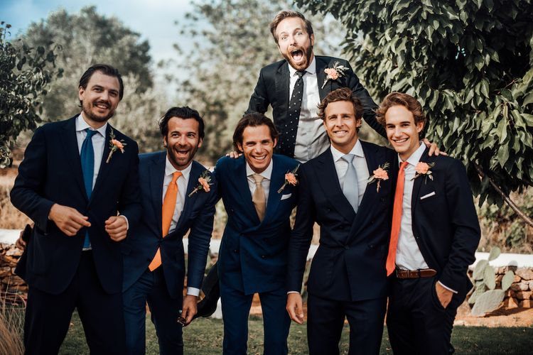 Groomsmen in navy suits and orange ties