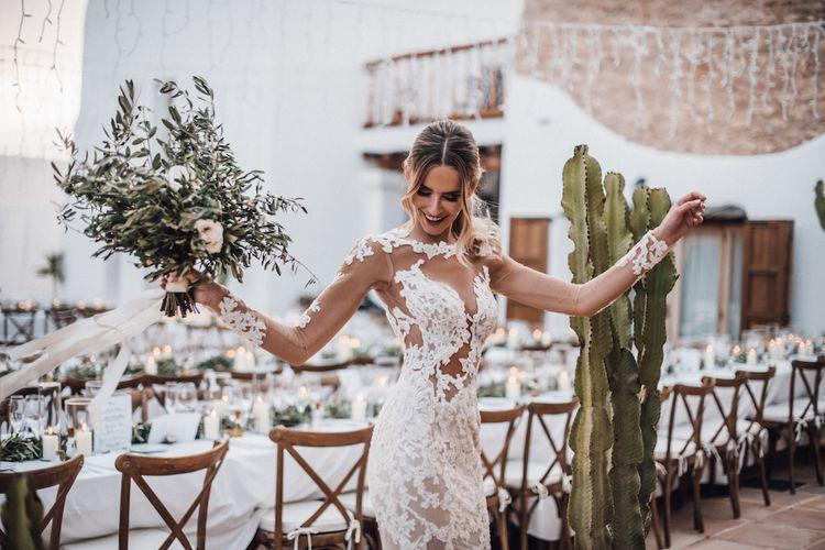 Beautiful boho bride in lace wedding dress with foliage bouquet