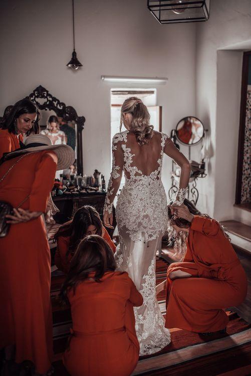 Wedding morning bridal preparations with bridesmaids in orange dresses