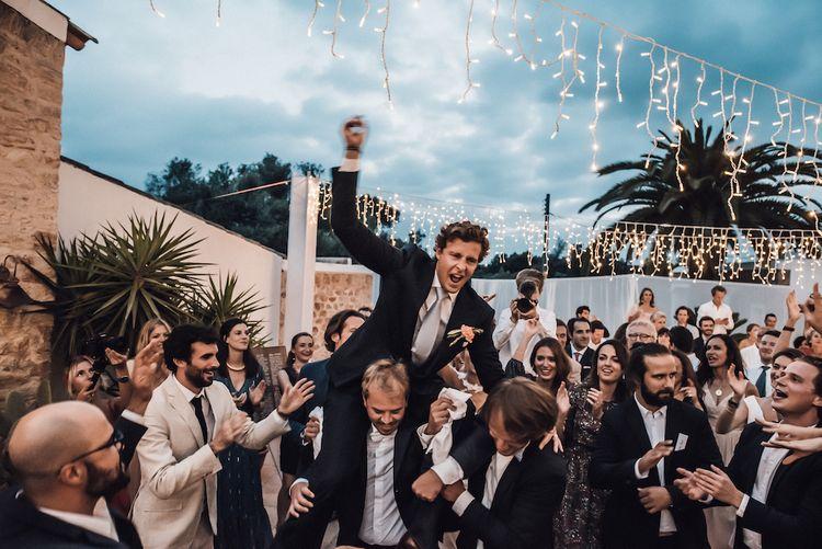 Groomsmen lifting the bride onto their shoulders at Ibiza wedding