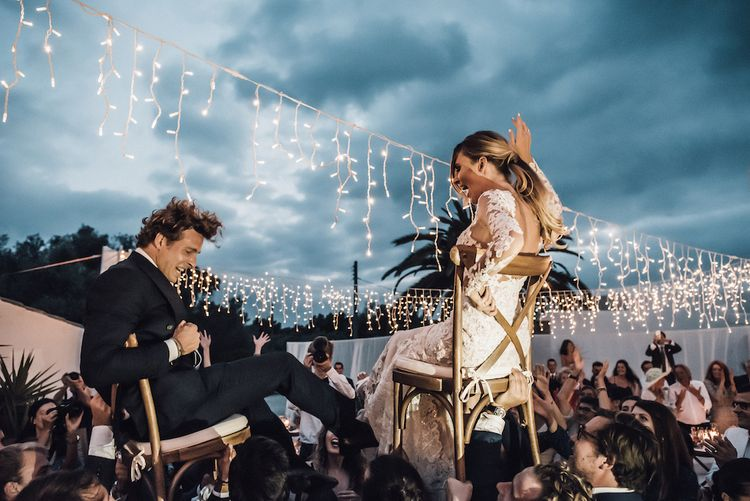Bride and groom being lifted in chairs at Ibiza wedding reception