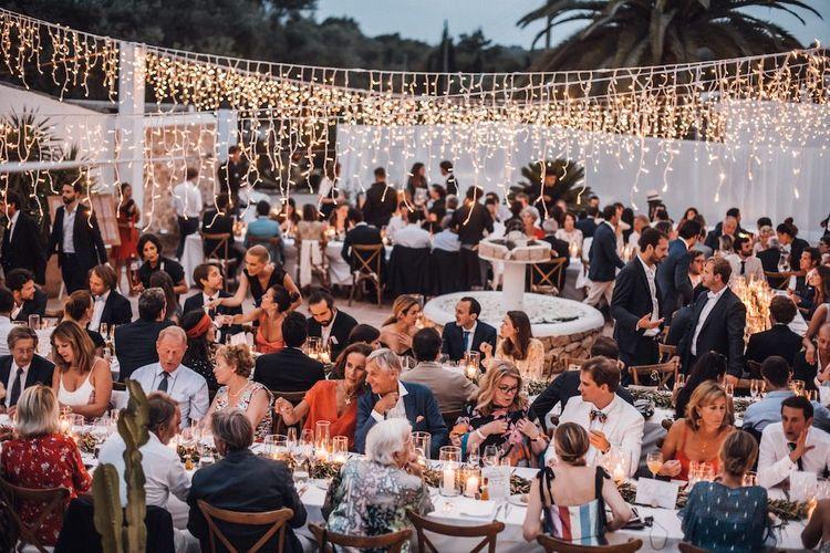 Outdoor Ibiza wedding reception with hanging fairy light decor