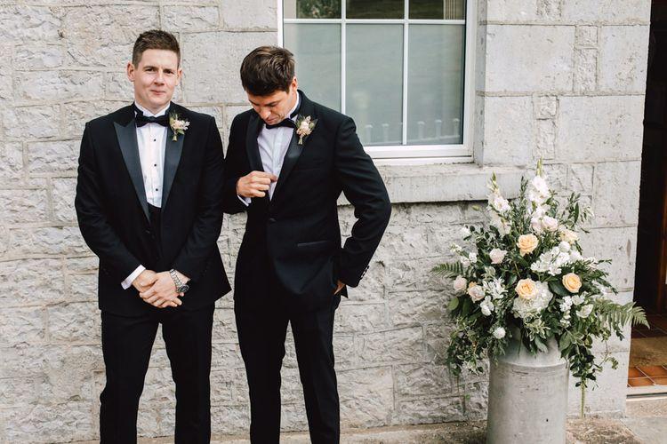 Groom wearing black tie at Wales wedding venue with peach flower displays