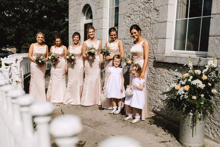 Peachy pink bridesmaid dresses with flower girls wearing white dresses at Wales wedding venue