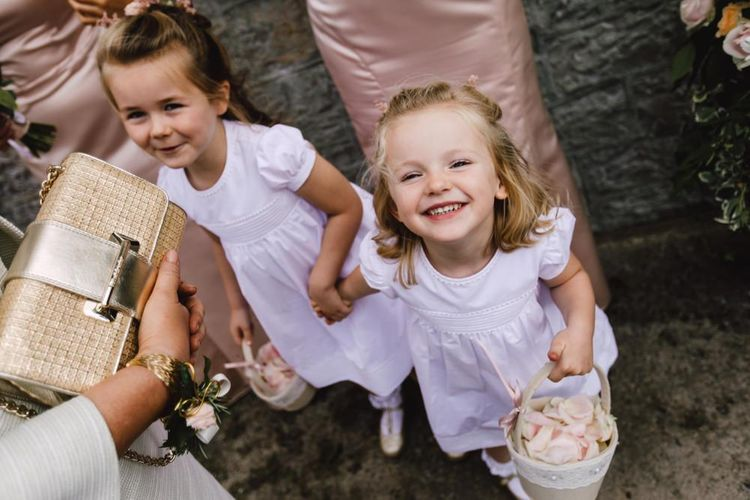 Flower girls wearing white dresses and petal confetti baskets at Wales wedding venue