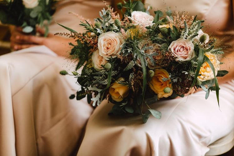 Peach and neutral floral bridesmaids bouquets at Wales wedding venue
