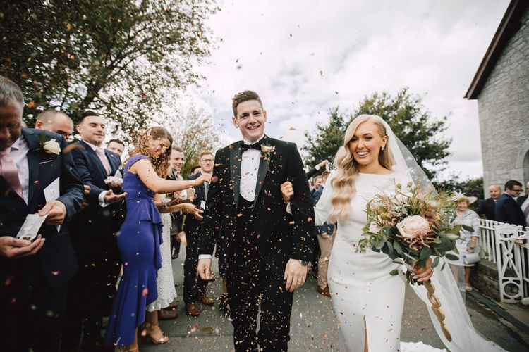 Bride and groom confetti exit with bride wearing split front dress and a long veil teamed with rose floral bouquet