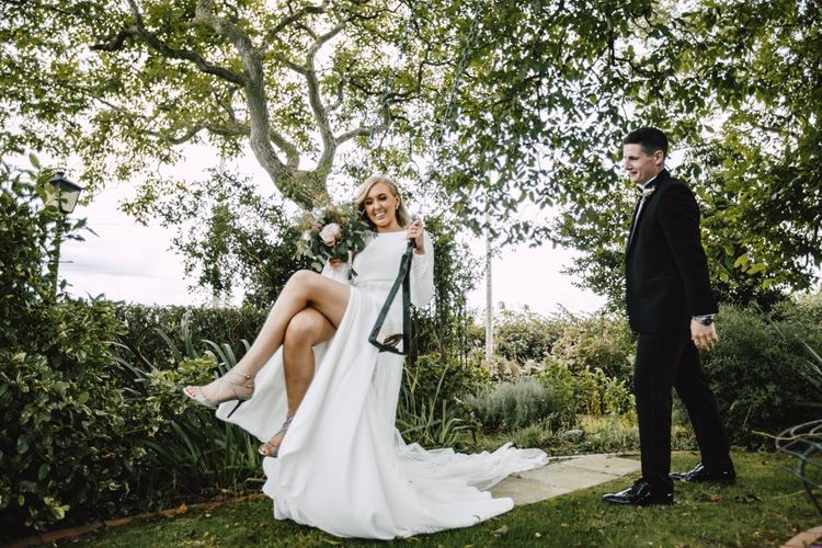 Bride and groom at Wales wedding venue wearing split front dress and lace tipped long veil
