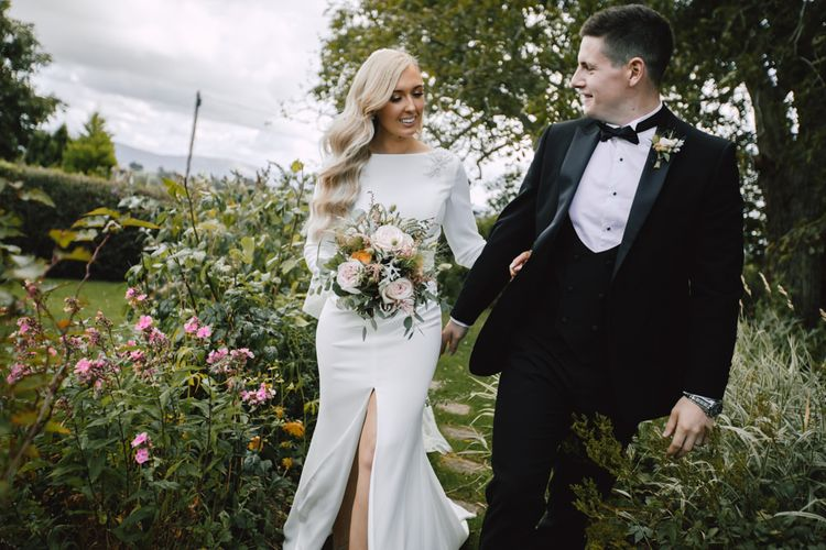 Bride and groom at autumn celebration wearing split front dress with lace tipped long veil and groom in black tie