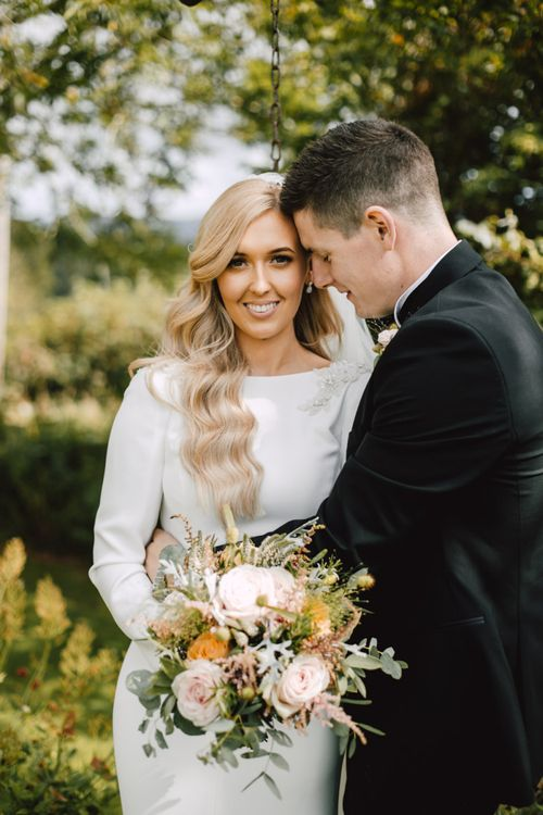 Bride and groom embrace at Welsh celebration with peachy pink floral bouquet