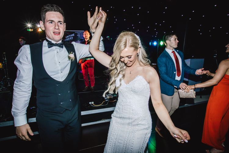 Bride and groom celebrate at their marquee reception wearing strapless evening gown