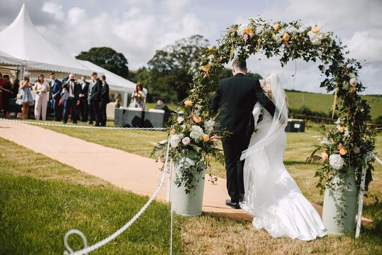 Bride and groom arrive at marquee reception with floral arch display