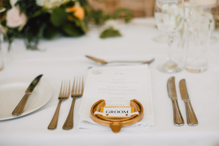 Horseshoe place settings sprayed in gold at marquee reception in Wales