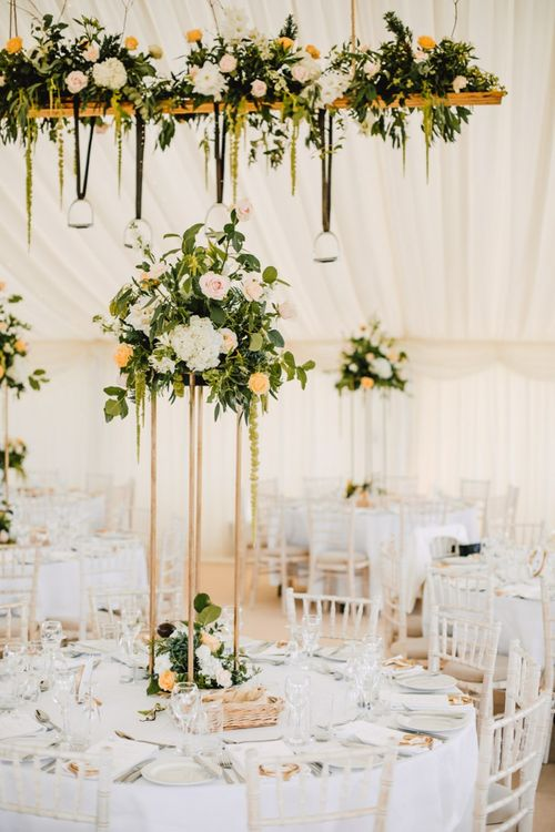 Marquee decor with floral installations and hanging stirrup displays
