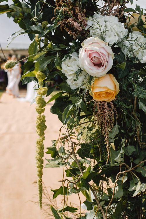 Details of flower arch with peach and pink rose floral touches at Wales wedding venue