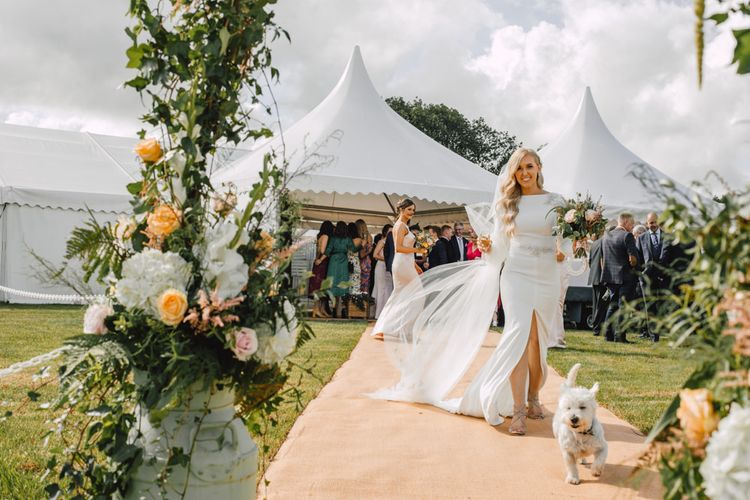 Bride wearing a classic split front wedding dress and long lace tipped veil at marquee reception with dog