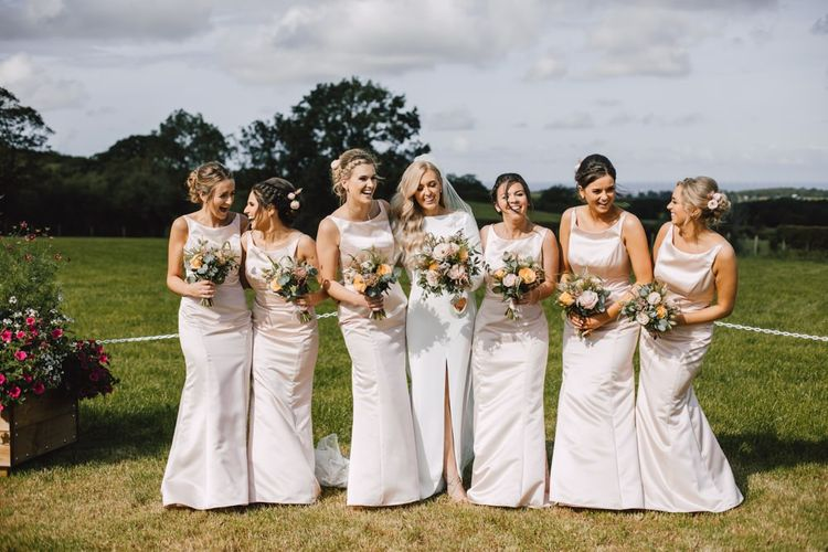 Bride and her bridesmaids wearing peachy pink bridesmaid dresses and floral bouquets at Wales wedding venue