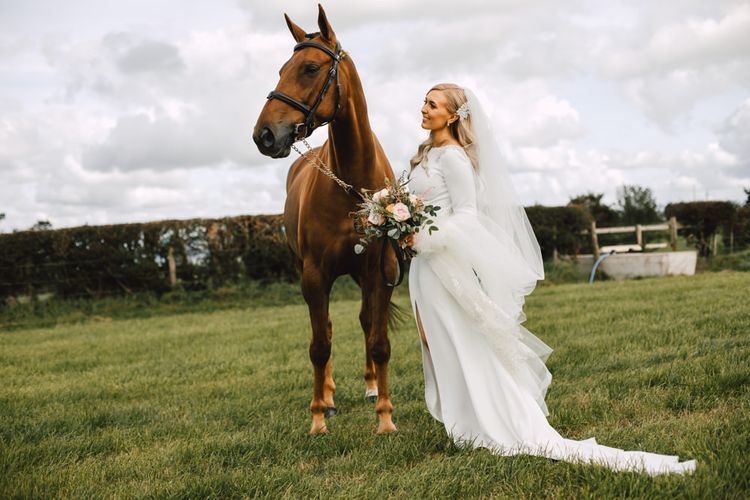 Bride wearing long lace tipped veil with her horse at marquee reception with equestrian touches