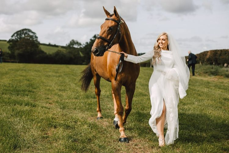 Bride wearing long lace tipped veil and split front bridal dress with her horse at marquee celebration with equestrian touches