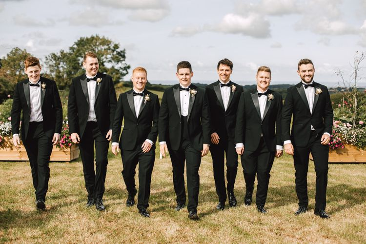 Groom and his groomsmen wearing black tie at marquee reception with blush and gold detailing