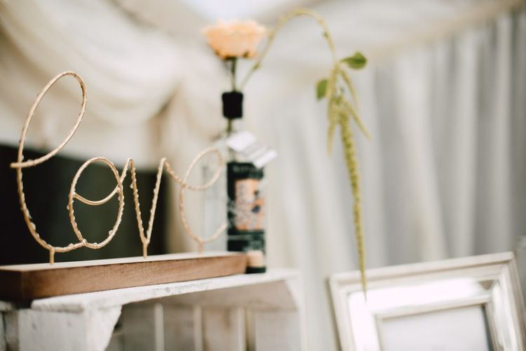 Gold 'love' sign with peach rose floral decor at marquee reception with equestrian details