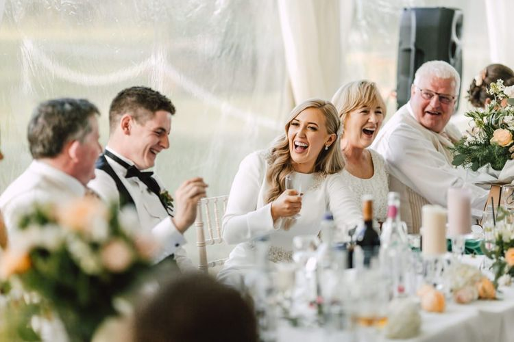 Bride and groom celebrate at their marquee reception with peachy pink rose floral decor