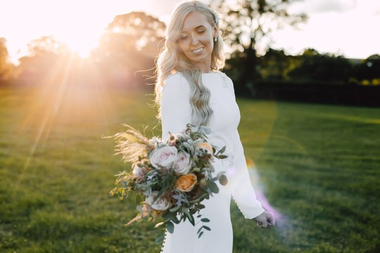 Bride wearing a simple split front wedding dress and peachy pink floral bouquet at marquee reception in autumn.