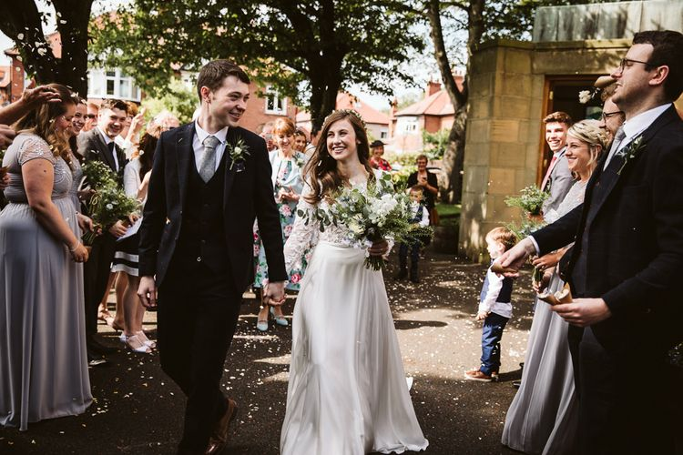 Confetti Moment with Bride in Long Sleeve Emma Beaumont Wedding Dress and Groom in Master Debonair Suit
