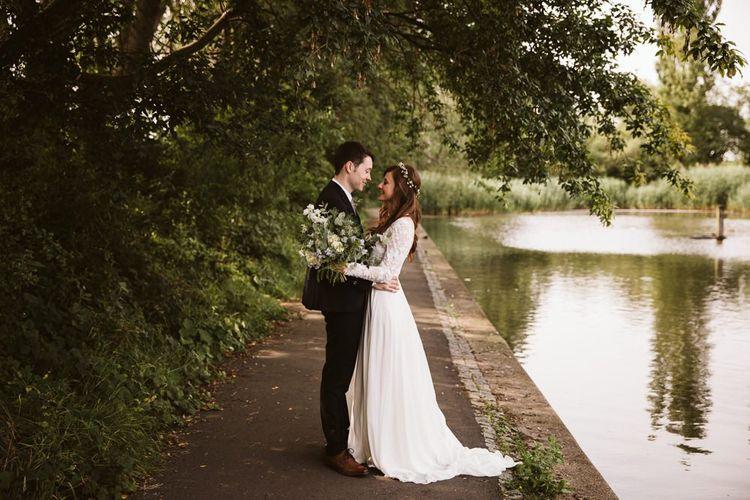 Bride in Applique Long Sleeve Emma Beaumont Wedding Dress and Groom in Master Debonair Suit by the Embankment