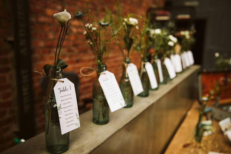 Bottle Table Plan Filled with Wildflowers and Luggage Tags
