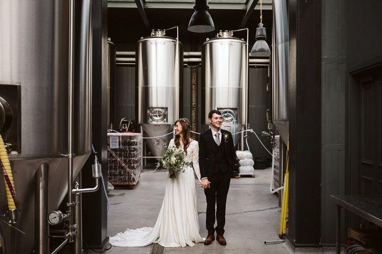 Bride in Emma Beaumont Wedding Dress and Groom in Master Debonair Suit Standing inside Wylam Brewery Wedding Venue in Newcastle