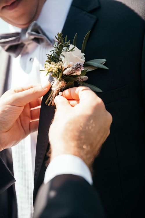 Blush Rose Buttonhole.  Grooms Morning Preparations. Marquee in Jersey. Foliage Installations. Stationery by Quints of Jersey. Bride Wears Enzoani. Photography by Max Burnett