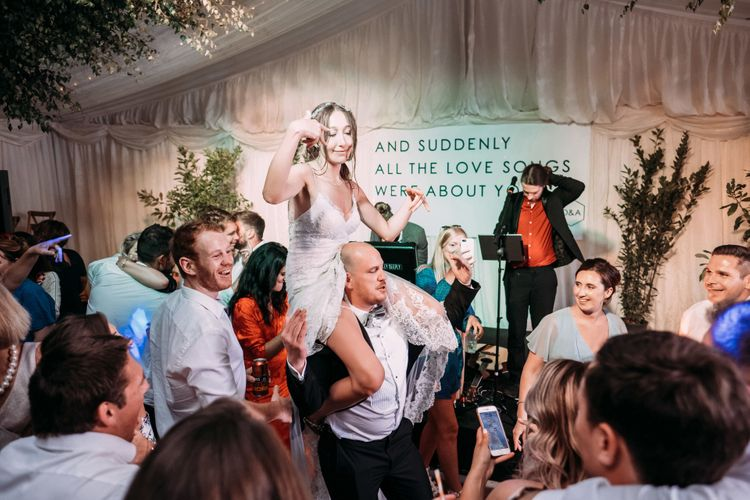 Bride Dancing. Large Format Printing and Signage. Marquee in Jersey. Foliage Installations. Stationery by Quints of Jersey. Bride Wears Enzoani. Photography by Max Burnett