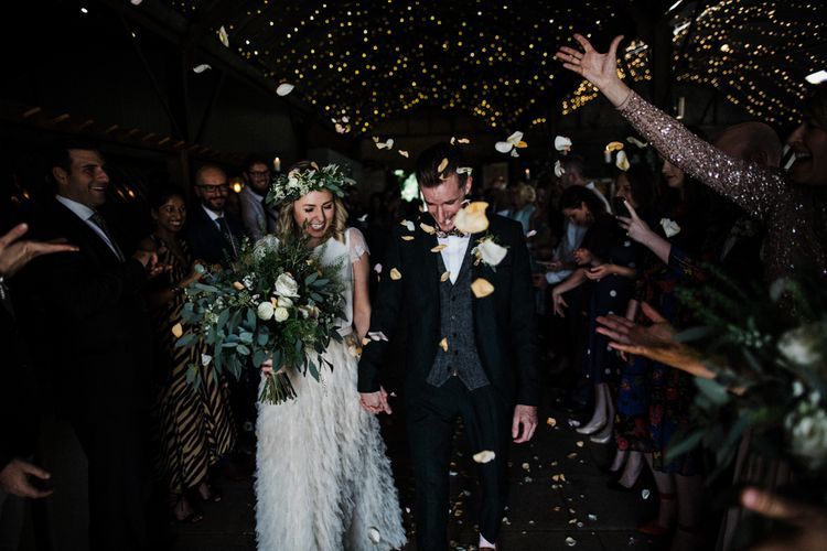 Confetti Moment with Bride in Halfpenny London Swan Tulle Petal Skirt and Flower Crown and Groom in Wool Suit and Bow Tie