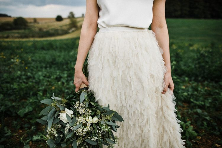 Bride in Stylish Halfpenny London Swan Tulle Petal Skirt Holding a White and Green Bouquet