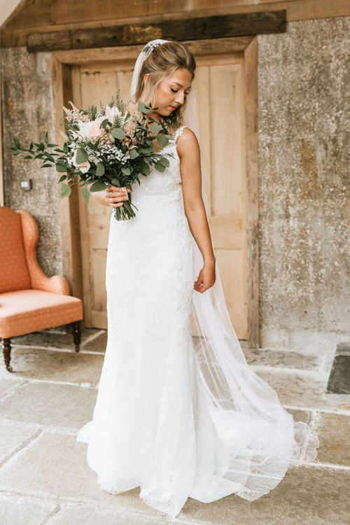 Bride in St Patrick wedding dress with blush bouquet