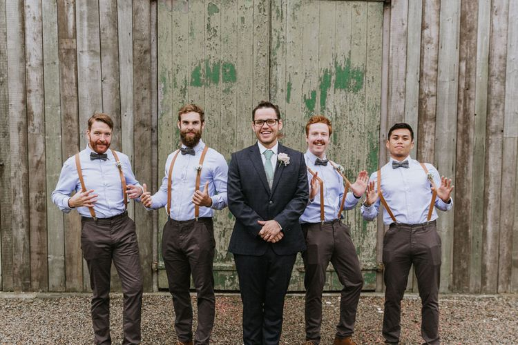 Groom in suit and groomsmen in bowties and braces