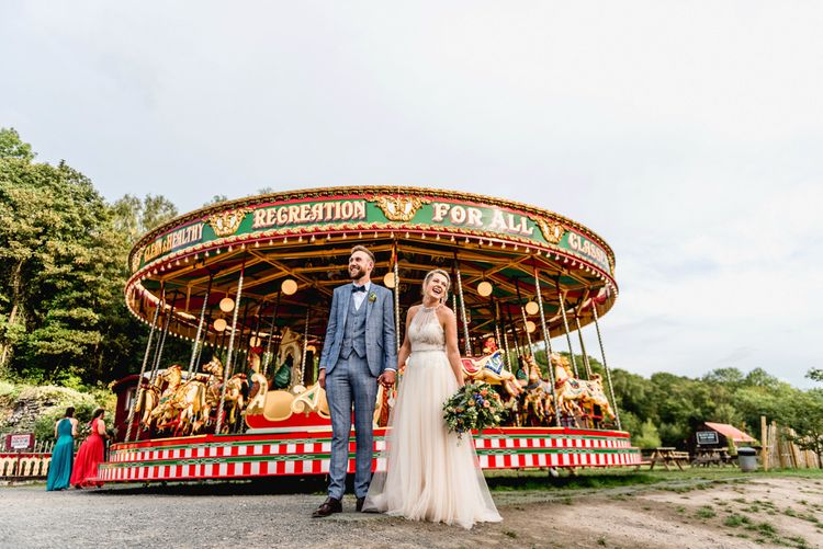 Vintage Carousel | Bride in Halterneck Tulle Allure Bridal Wedding Dress | Groom in  Blue Check Moss Bros. Suit | Vintage Fairground at Blists Hill Victorian Town Museum in Ironbridge | Lisa Carpenter Photographer