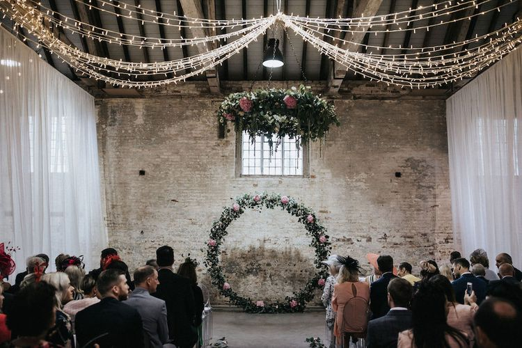 Ceremony Altar with Floral Moon Gate, Drapes and String Lights Wedding Decor