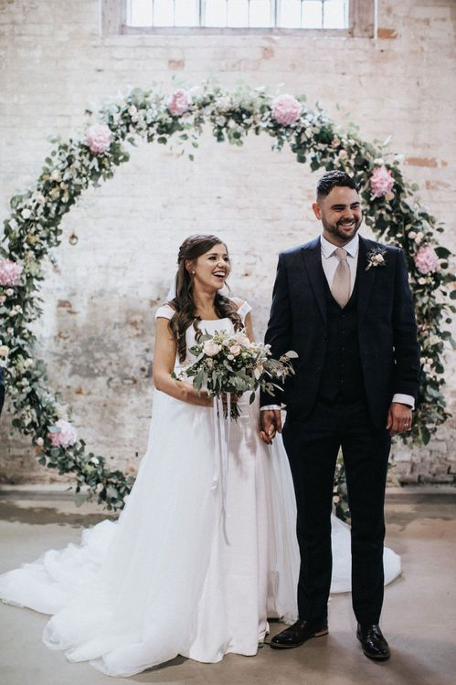 Bride and Groom Standing in Front of a Floral Moon Gate