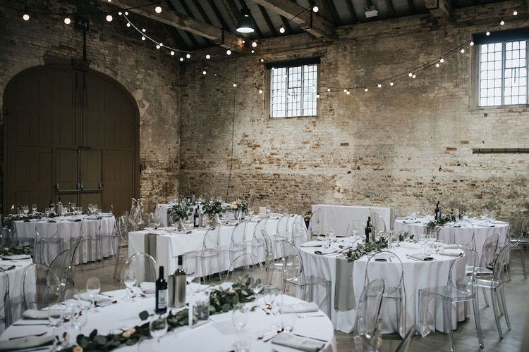 Elegant Wedding Reception Decor with Festoon Lights and Ghost Chairs